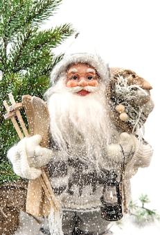 Père noël mignon avec arbre de noël et cadeaux dans la neige