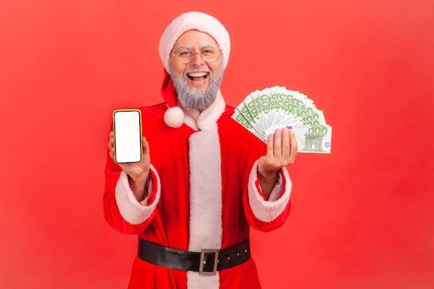 Père noël montrant des billets en euros et un smartphone avec écran blanc vierge.