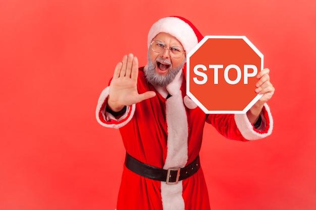 Père noël montrant un panneau d'arrêt rouge et une interdiction avec la paume, criant.