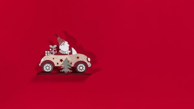 Père noël de noël dans une voiture avec un arbre et un cadeau sur fond rouge. notion de nouvel an