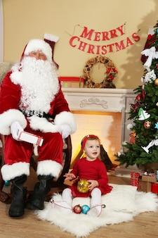 Père noël offrant un cadeau à une petite fille mignonne près de la cheminée et de l'arbre de noël à la maison