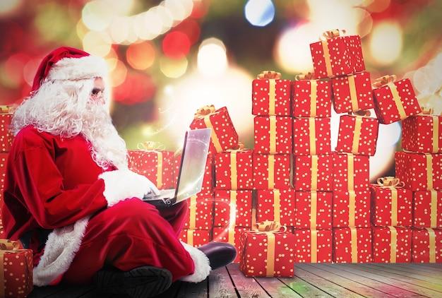 Père noël avec un ordinateur portable et des coffrets cadeaux