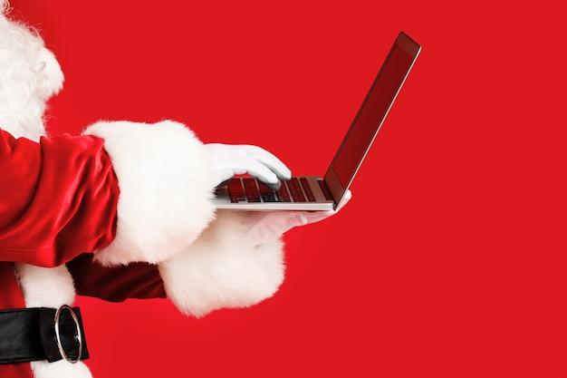 Père noël avec ordinateur portable sur rouge