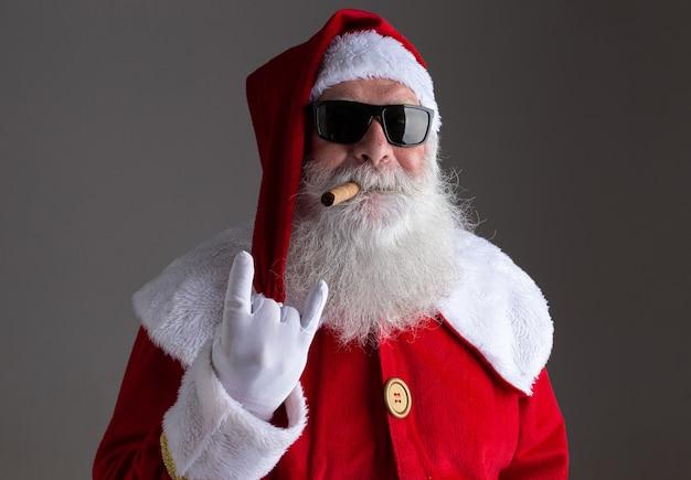 Père noël portant des lunettes de soleil montrant le signe de la main à bascule et fumant un cigare sur fond sombre