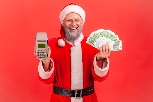 Père noël regardant la caméra avec le sourire, tenant un terminal et des billets en euros.