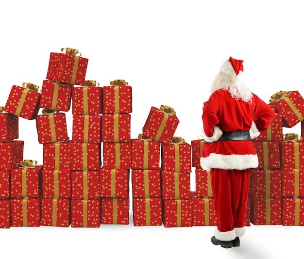 Le père noël regarde des tas de cadeaux de noël
