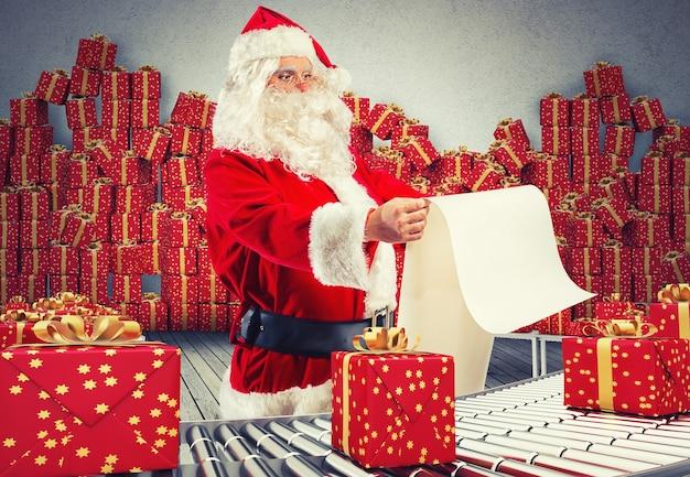 Père noël de rendu 3d vérifiant sur la liste des coffrets cadeaux de noël et emballés sur un rouleau de convoyeur