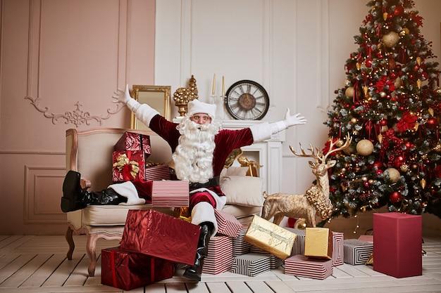Le père noël s'est allongé sur le canapé avec un tas de cadeaux près de la cheminée et du sapin de noël. nouvel an et joyeux noël, concept de joyeuses fêtes