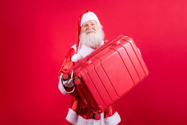 Père noël avec sa valise. concept de voyage du nouvel an. père noël à l'aéroport.
