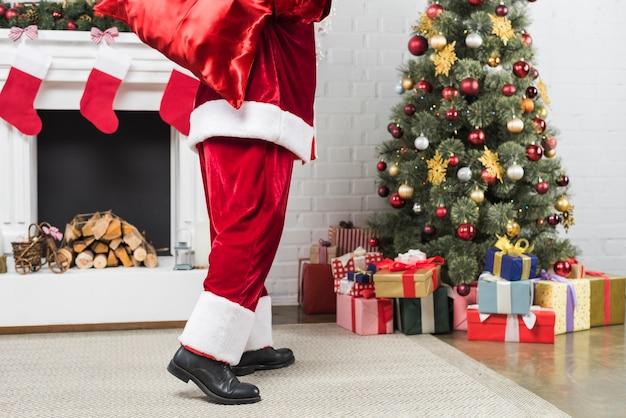 Père noël avec sac de cadeaux derrière le dos allant à l'arbre de noël