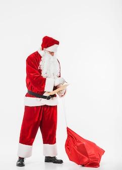 Père noël avec sac de cadeaux et liste d'enfants