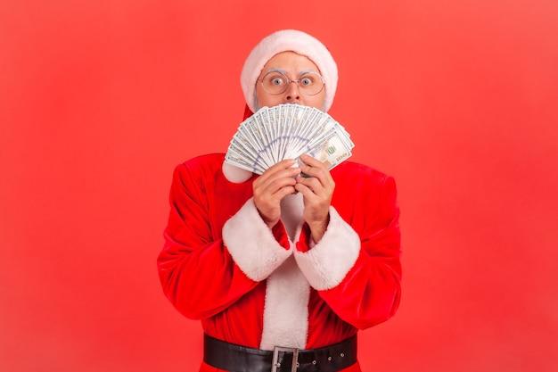Père noël se cachant le visage avec un fan de billets de banque en dollars, gagnant une grosse somme d'argent.