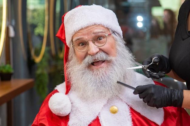 Père noël se rasant dans un salon de coiffure. se préparer pour noël. embellir pour les vacances. barbu. couper.