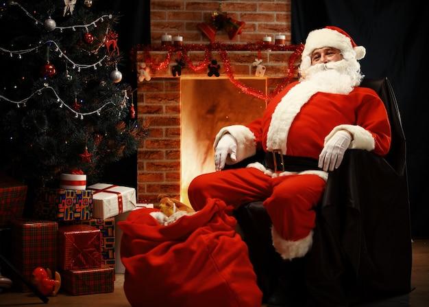 Père noël se reposer dans une chaise confortable près de la cheminée à la maison