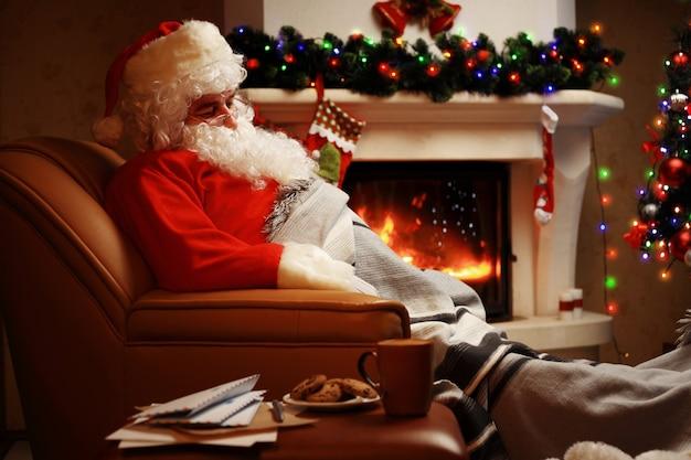 Père Noël Se Reposer Dans Une Chaise Confortable Près De La Cheminée à La Maison Photo Premium