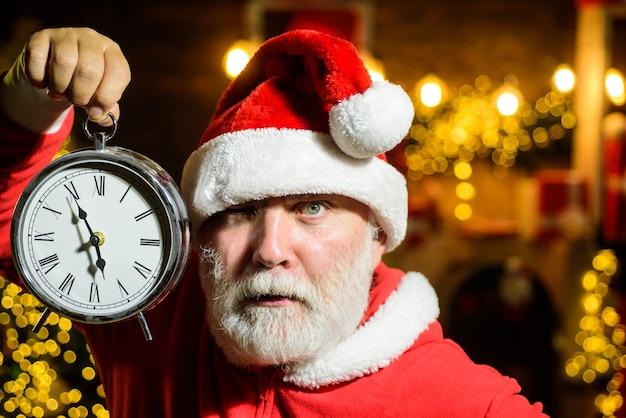 Le père noël sérieux tient l'horloge du nouvel an réveil du nouvel an réveil de noël vacances d'hiver le temps de