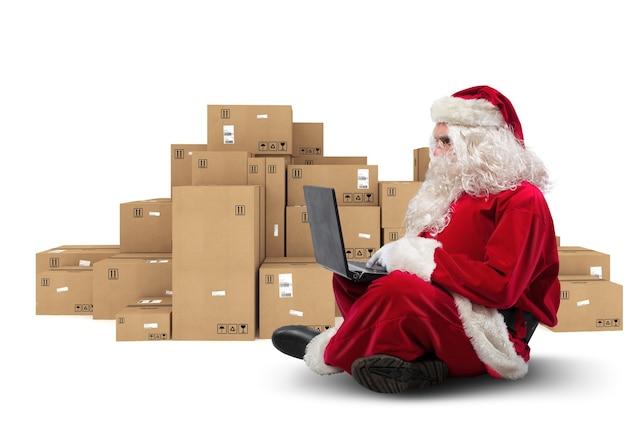 Le père noël technologique assis avec un ordinateur portable achète des cadeaux de noël avec le commerce électronique