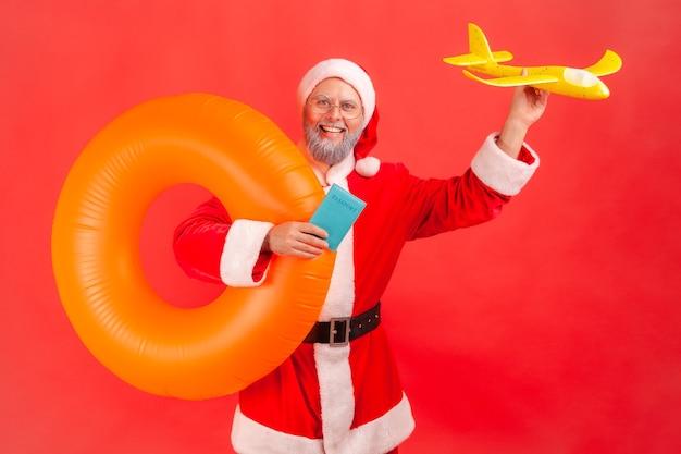 Père noël tenant un anneau en caoutchouc orange, un avion en papier et un passeport, voyageant pendant les vacances d'hiver.