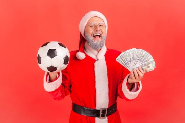 Père noël tenant un ballon de football et des billets en dollars, pariant et gagnant.