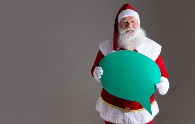 Père noël tenant un ballon de texte vierge.