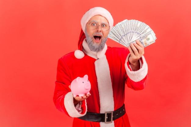 Père noël tenant des billets de banque en dollars et tirelire, épargne, dépôt à taux élevé.