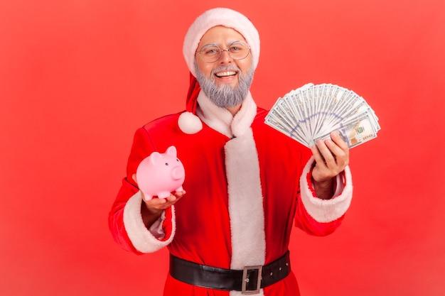 Le père noël tenant des billets de banque en dollars et une tirelire, se réjouissant des économies.
