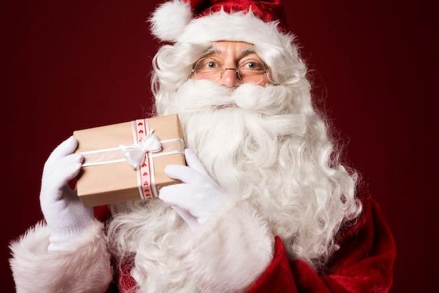 Père noël tenant une boîte-cadeau