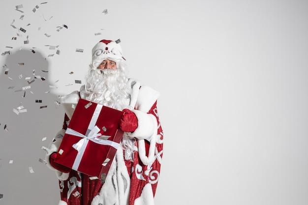 Père noël tenant un cadeau de noël enveloppé étant douché de confettis d'argent.