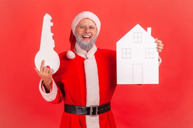 Le père noël tenant dans les mains une maison en papier et une clé, étant heureux d'acheter un nouvel appartement.