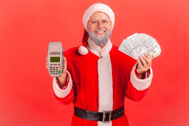 Père noël tenant en mains des billets de banque en dollars et un terminal, paiement sans contact.