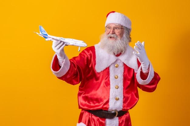 Père noël tenant un petit avion jouet sur fond jaune. concept de voyage de noël