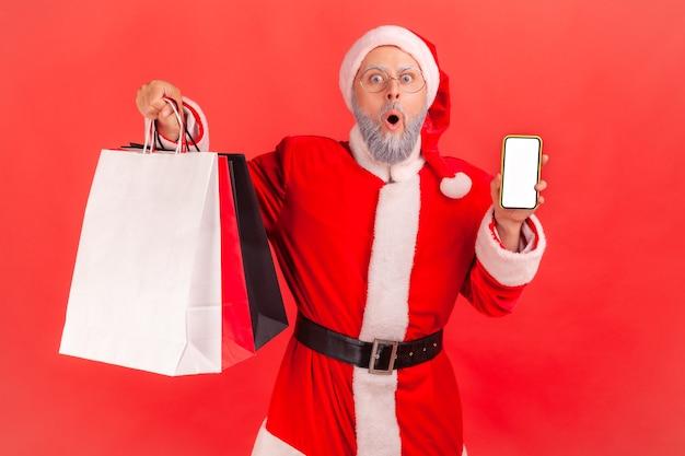 Le père noël tenant des sacs à provisions et un téléphone avec un écran vide, choqué par les remises de noël