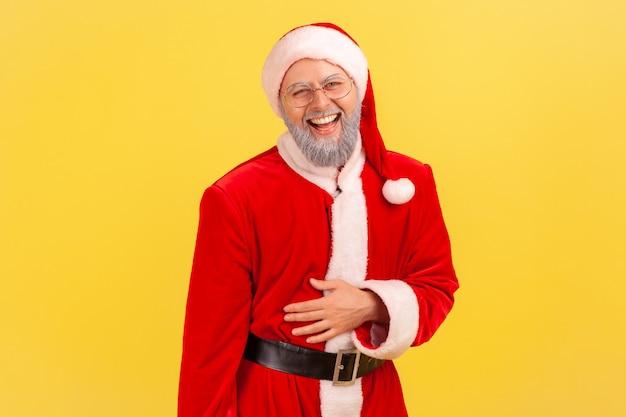 Père noël tenant son ventre et riant à haute voix, entendant une histoire ou une blague drôle.