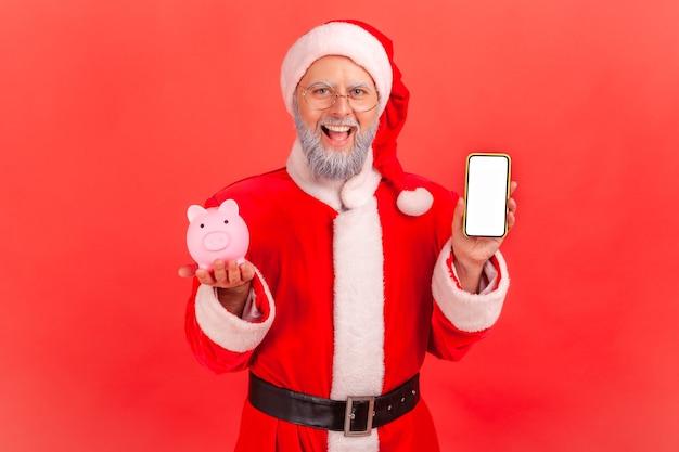 Père noël tenant un téléphone intelligent avec écran blanc blanc et tirelire, remise en argent, portefeuille en ligne.
