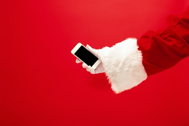 Père noël tenant un téléphone portable prêt pour la période de noël sur fond de studio rouge. la saison, hiver, vacances, célébration, concept de cadeau