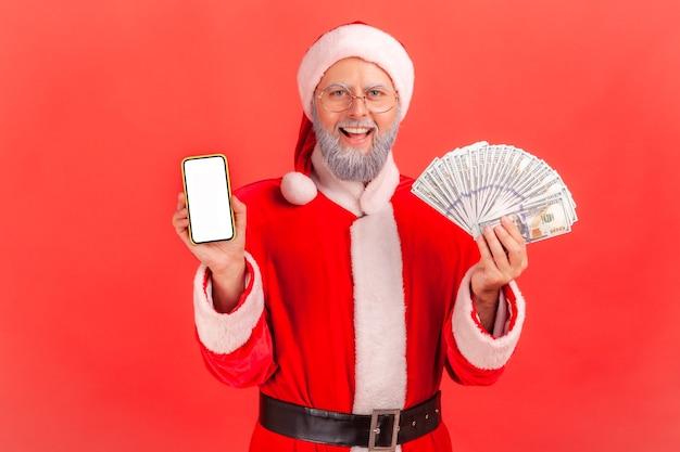 Père noël tenant un ventilateur d'argent et montrant un smartphone avec un écran blanc blanc.