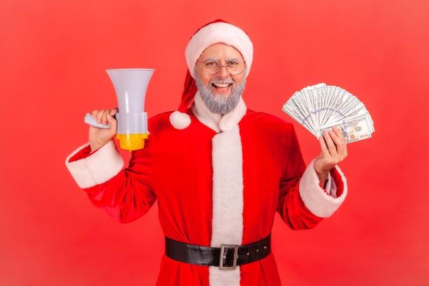 Père noël tenant un ventilateur de billets de banque et de mégaphones, regardant la caméra avec une expression heureuse.