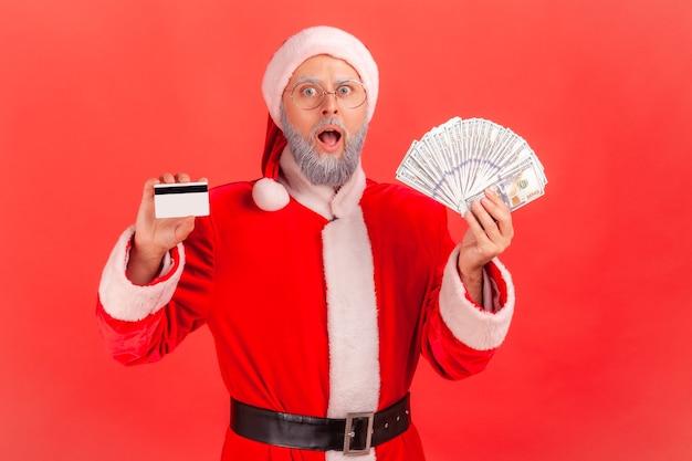 Père noël tenant un ventilateur de dollars et de carte de crédit, étonné d'un gros cashback.