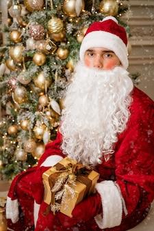 Le père noël tient un cadeau dans des mitaines sur une ambiance festive d'arbre de noël