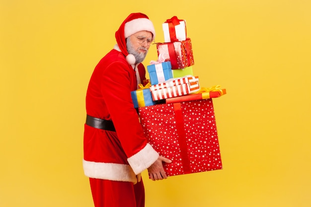 Le père noël transportant de nombreuses boîtes avec des cadeaux, se préparant pour les fêtes de noël.
