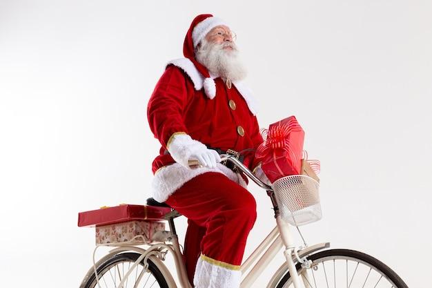 Père noël à vélo offrant des cadeaux de noël.