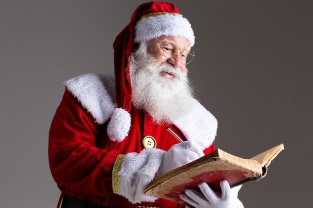 Père noël avec un vieux livre de couverture rouge. notez les noms des cadeaux pour noël. noël approche