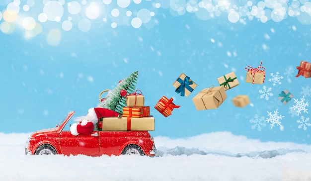 Père noël en voiture jouet rouge offrant des cadeaux de noël ou des cadeaux du nouvel an sur fond neigeux. carte de vacances. espace de copie.