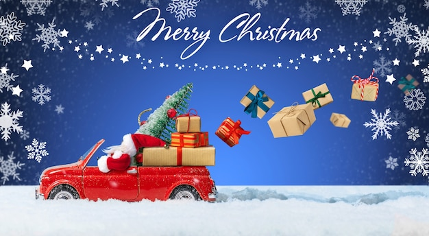 Père noël en voiture jouet rouge offrant des cadeaux de noël ou des cadeaux de nouvel an sur fond bleu d'hiver. carte de vacances de noël, fond, bannière.