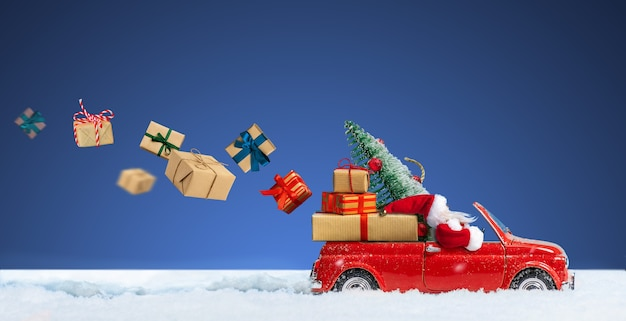 Père noël en voiture rouge livrant des coffrets cadeaux de noël ou du nouvel an sur un fond bleu neigeux.