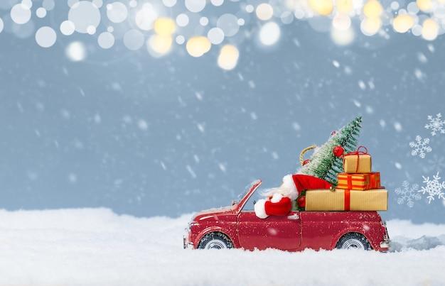 Père noël en voiture rouge livrant un sapin de noël et des cadeaux sur fond de neige. fond de noël ou du nouvel an. carte de vacances. espace de copie.