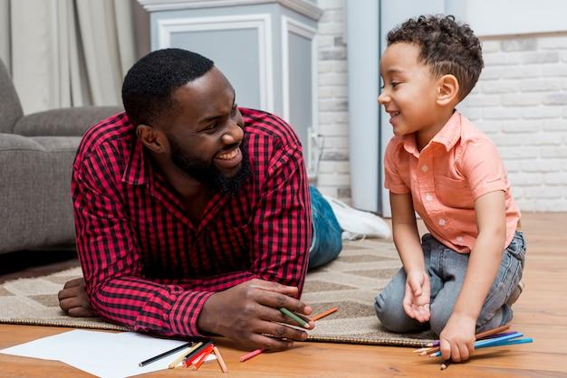 Père noir et fils avec des crayons au sol