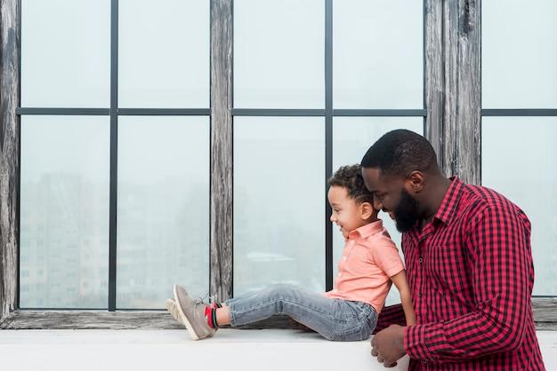 Père noir, fils, debout, à, rebord fenêtre