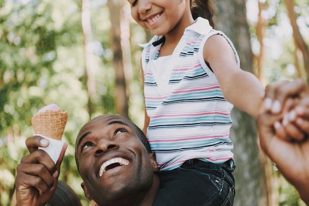 Père noir porte fille sur cou en forêt.