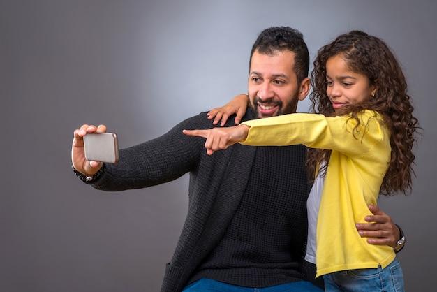 Père noir prenant des selfies avec sa fille